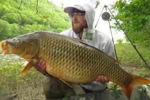 Evolution Team Member Adam holding a large carp